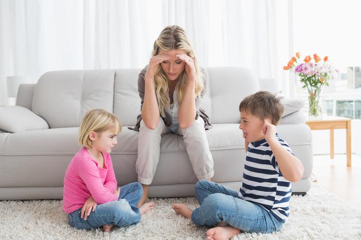 Fedupmotherlisteningtoheryoungchildrenfightathomeinthelivingroom